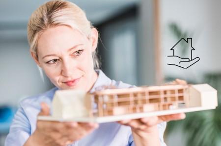 Frau hält das Modell eines Hauses