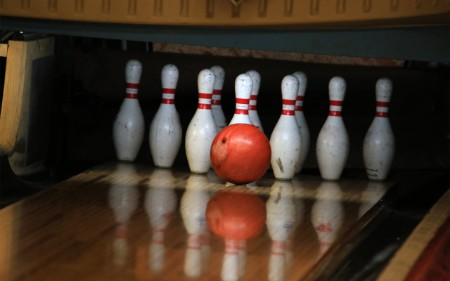 Ball striking pins in bowling alley