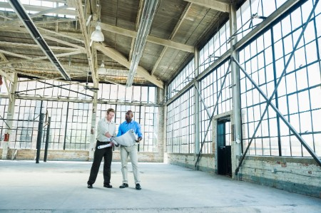 business people looking blueprints warehouse