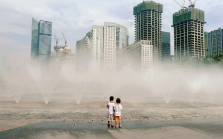 Children looking out onto a fountain and cityscape.