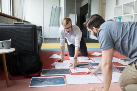 colleagues planning brainstorming paper floor