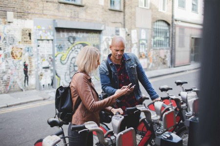 couple using mobile phones bicycle sharing system