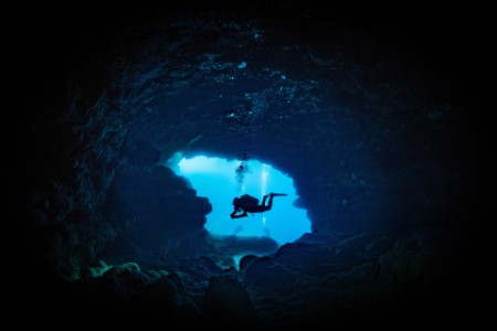 Diver in mouth of underwater cave