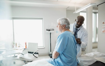 A doctor checks the heartbeat of a senior man