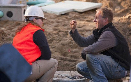 Female engineer discussing with a man at a construction site.
