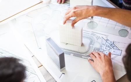 Mãos femininas a trabalhar numa maquete de arquitetura.
