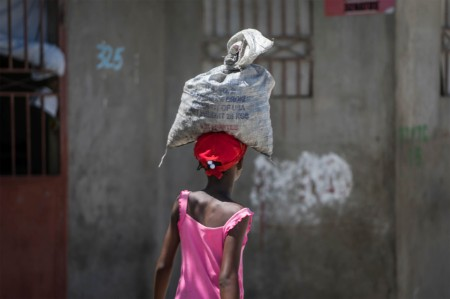 haitian woman carries white sack head