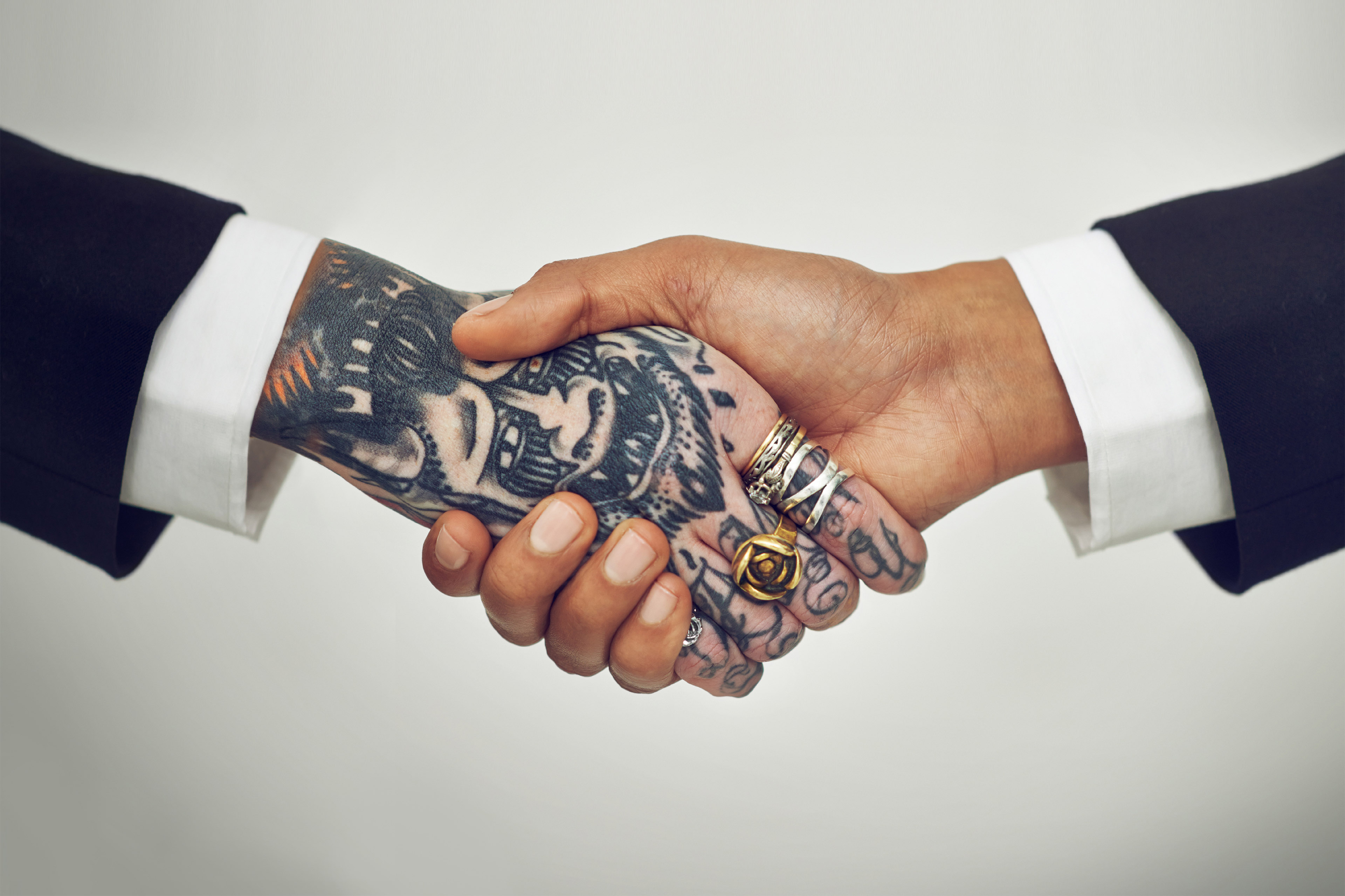 Handshake between a tattooed hand and unmarked hand