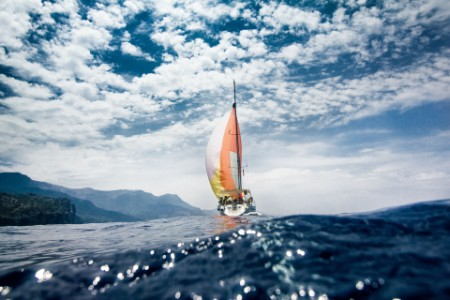 Low angle boat sailing in the sea and cloudy sky islands