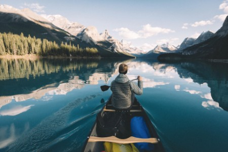 Man in canoe paddles across a lake in canada