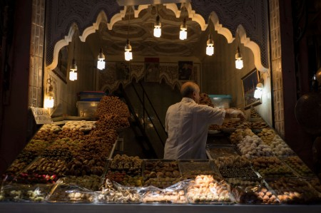 man marrakech morocco selling produce market hanging lightbulbs
