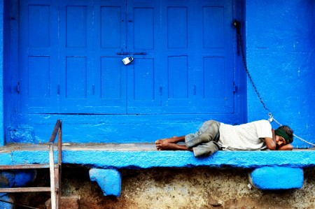 man sleeps steps bright blue building