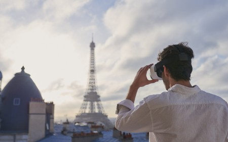 Man with VR headset looking towards Eiffel Tower.