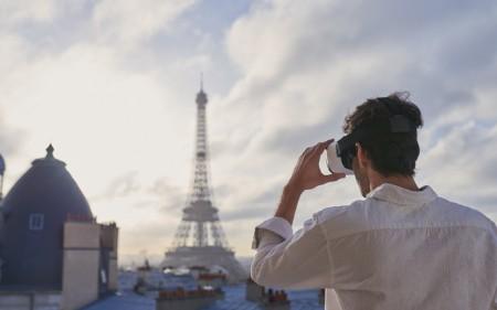 Homem com dispositivo de realidade virtual a olhar para a Torre Eiffel.