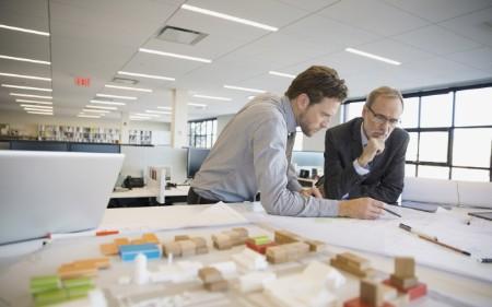 Dois homens a olhar para desenhos a pensar no futuro.