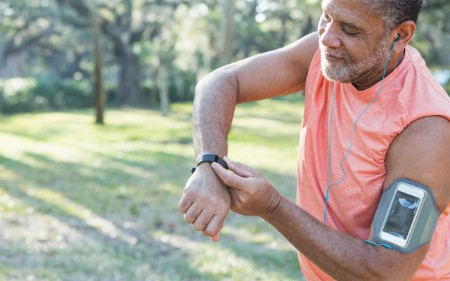 An older man checks his wearable out running