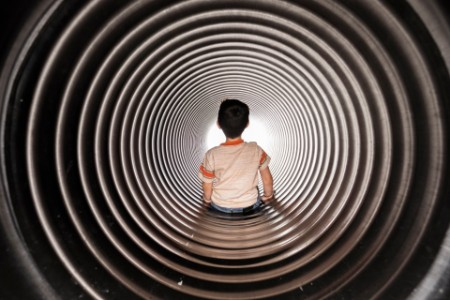 Rear view of boy sitting in huge metallic pipe