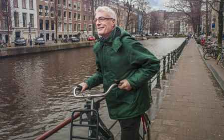 A senior man rides a bike by a canal
