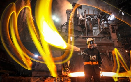 Steelworker with molten metal taken from furnace