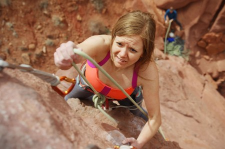 woman climbs rock
