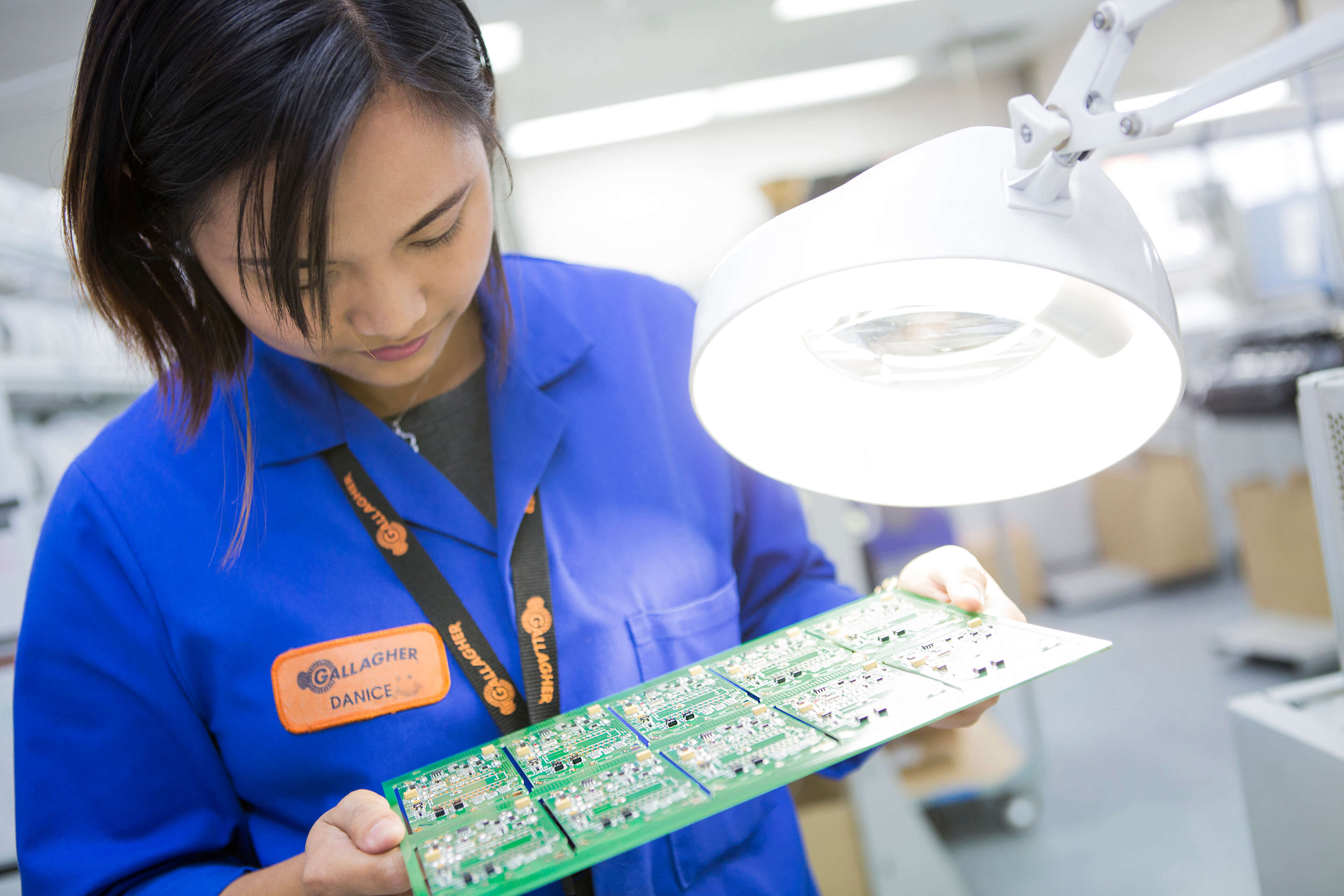Woman examining motherboard in Gallagher's production facilities