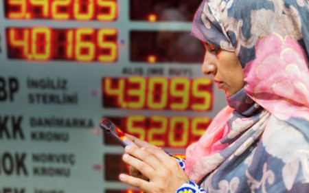 A woman in a scarf checks her phone in front of a currency board