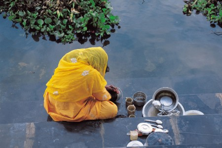 woman washing pots river