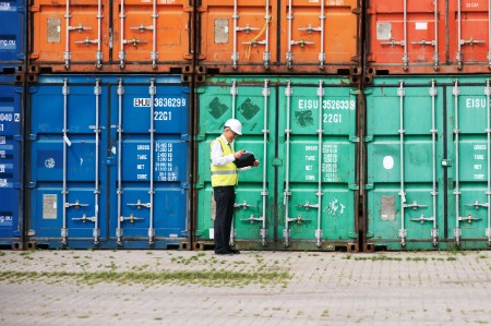 Man with clipboard in front of stacked shipping containers
