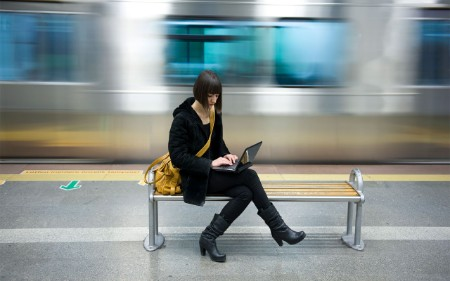 young woman in subway working on a laptop