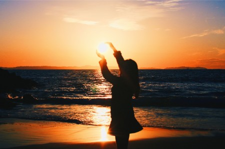 Silhouette of woman holding sun on beach at sunset