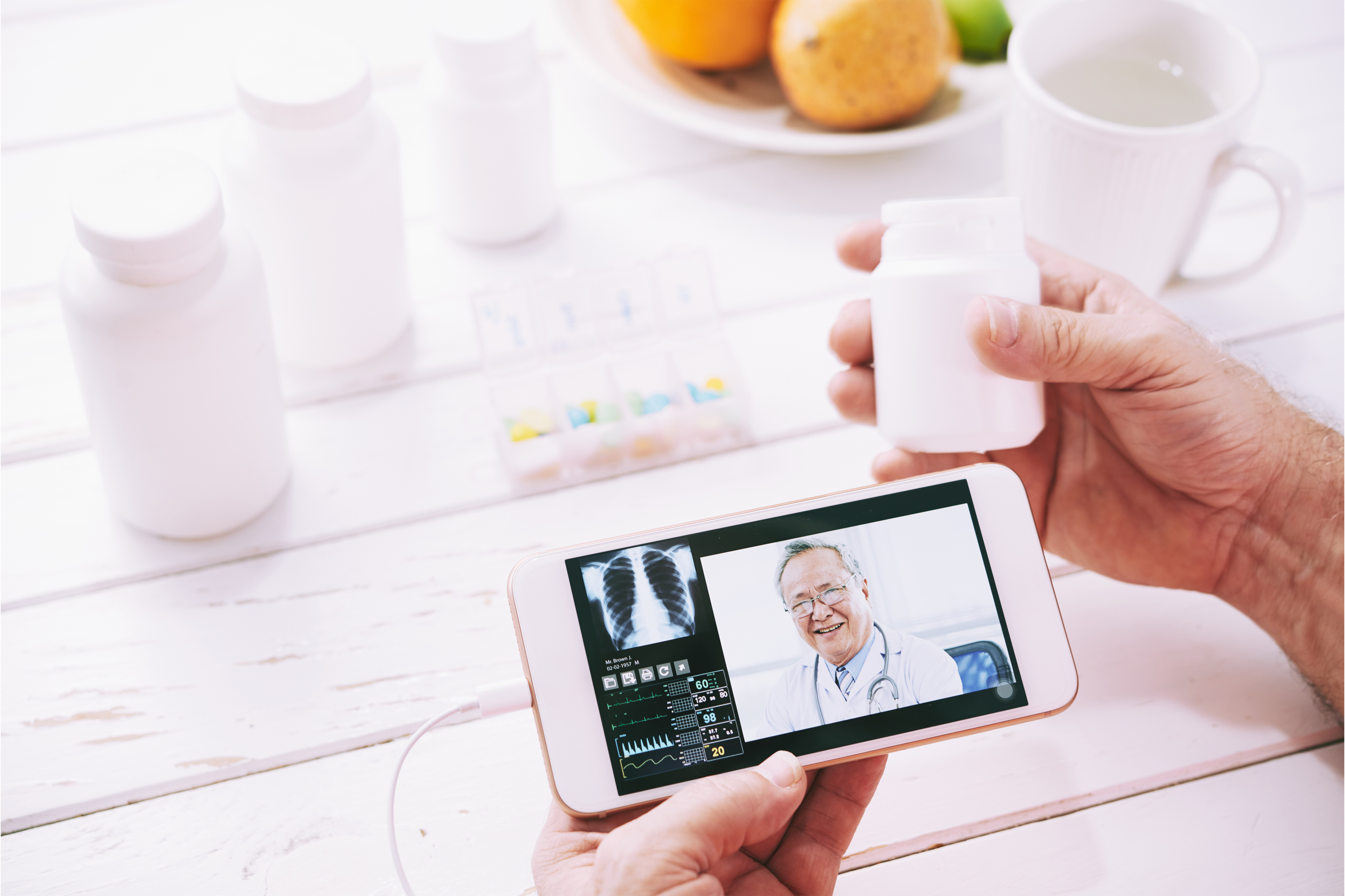 Hands of aged patient consulting online on his smartphone