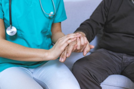 Patients hand supported by family caregiver