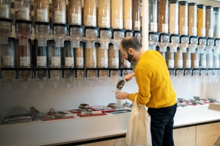 Man filling jar with serving scoop at zero waste store