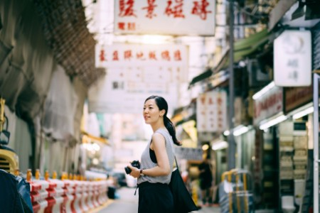 Beautiful young woman carrying camera exploring city
