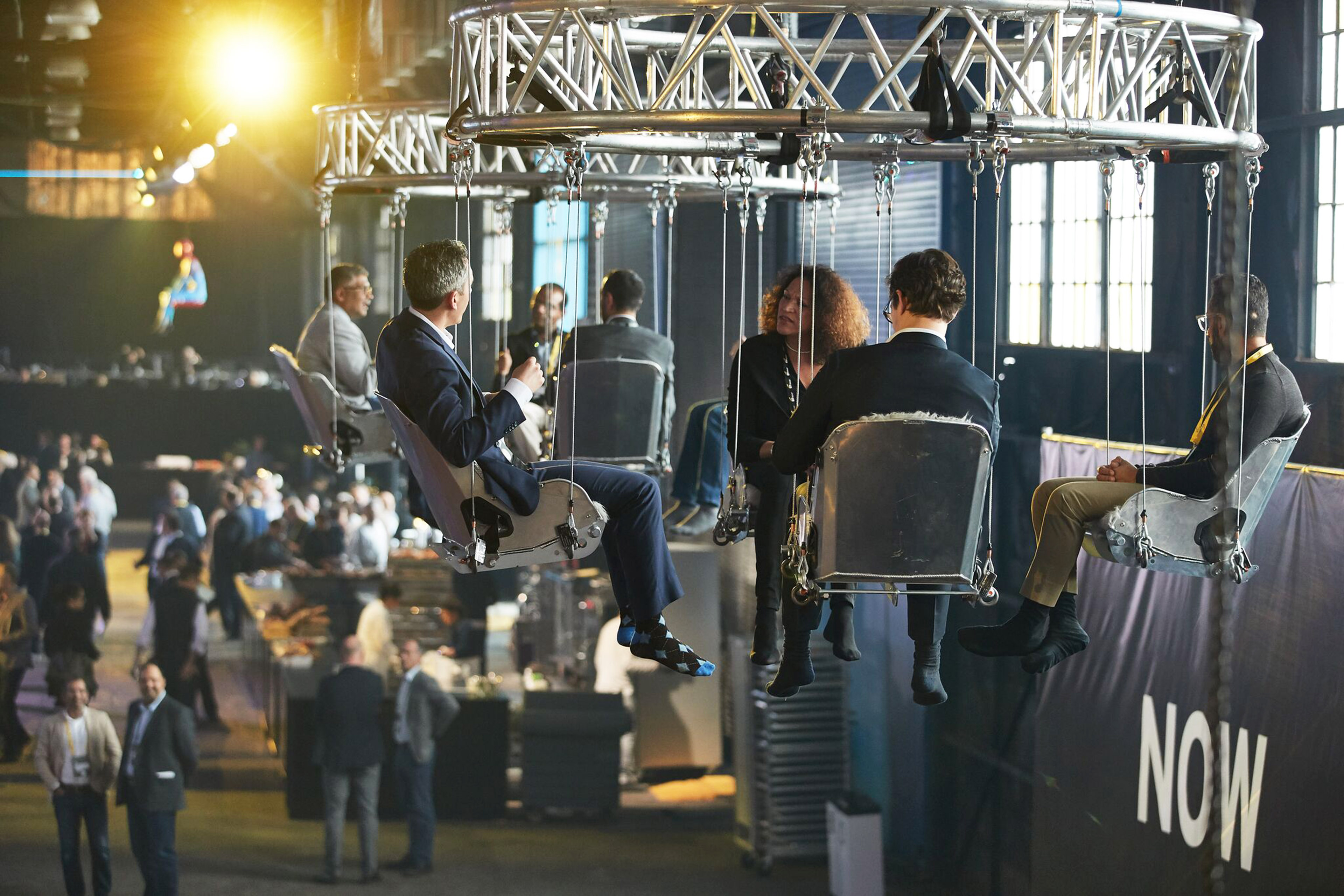 People sitting in hanging chairs at Innovation realized event image