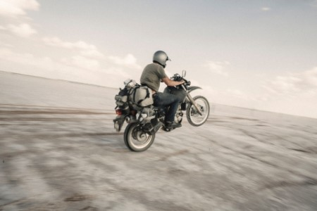 Male biker riding motorbike on desert road against skyImage downloaded by Charlie Brewer at 14:51 on the 10/06/19