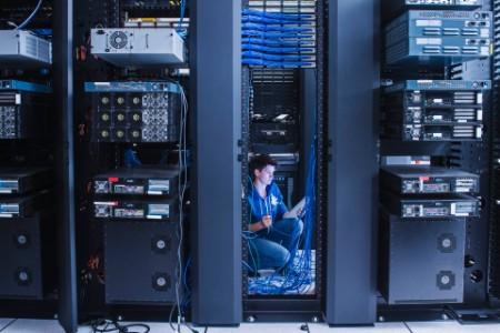 Mulher organizando cabos em sala de servidores