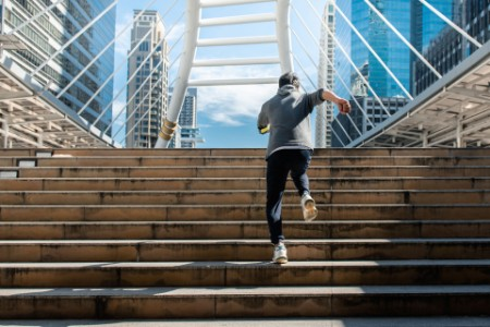 Man running up stairs towards bridge