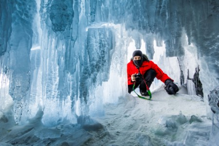 Photographer in the ice cave sunset lake Baikal Russia