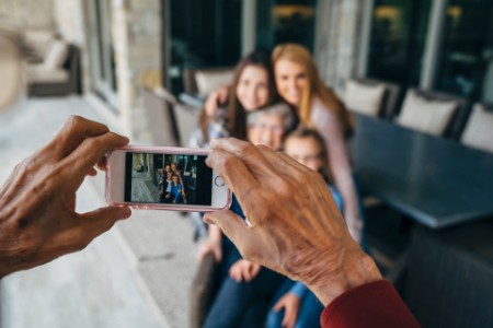 Hands senior man photographing family smart phone porch