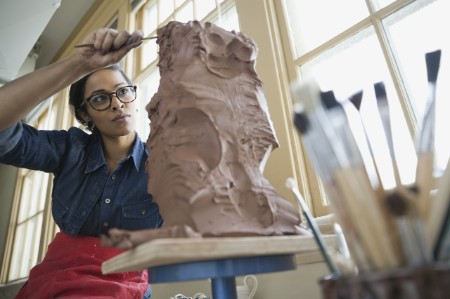 Artist and clay sculpture
