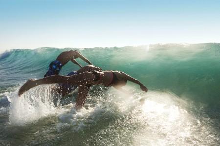friends diving waves beach
