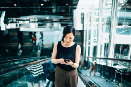 asian businesswoman reading emails on smartphone on escalator