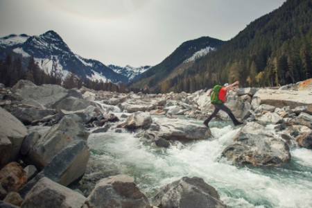 Backpacker jumps boulders to cross a raging river in the wilderness