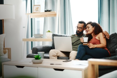 Couple using a credit card while going over their finances at home