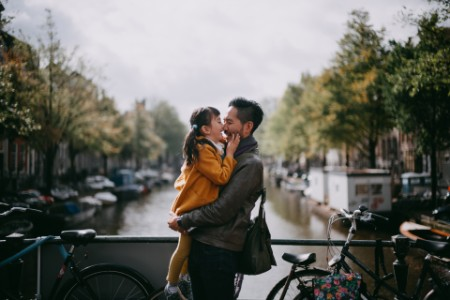 Father holding child on bridge over canal