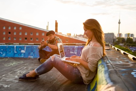 young adults sitting on a roof working