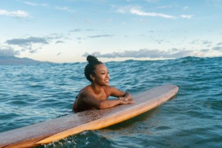 Young woman resting on her surfboard waiting