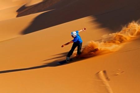 sand boarder speeds down the dunes