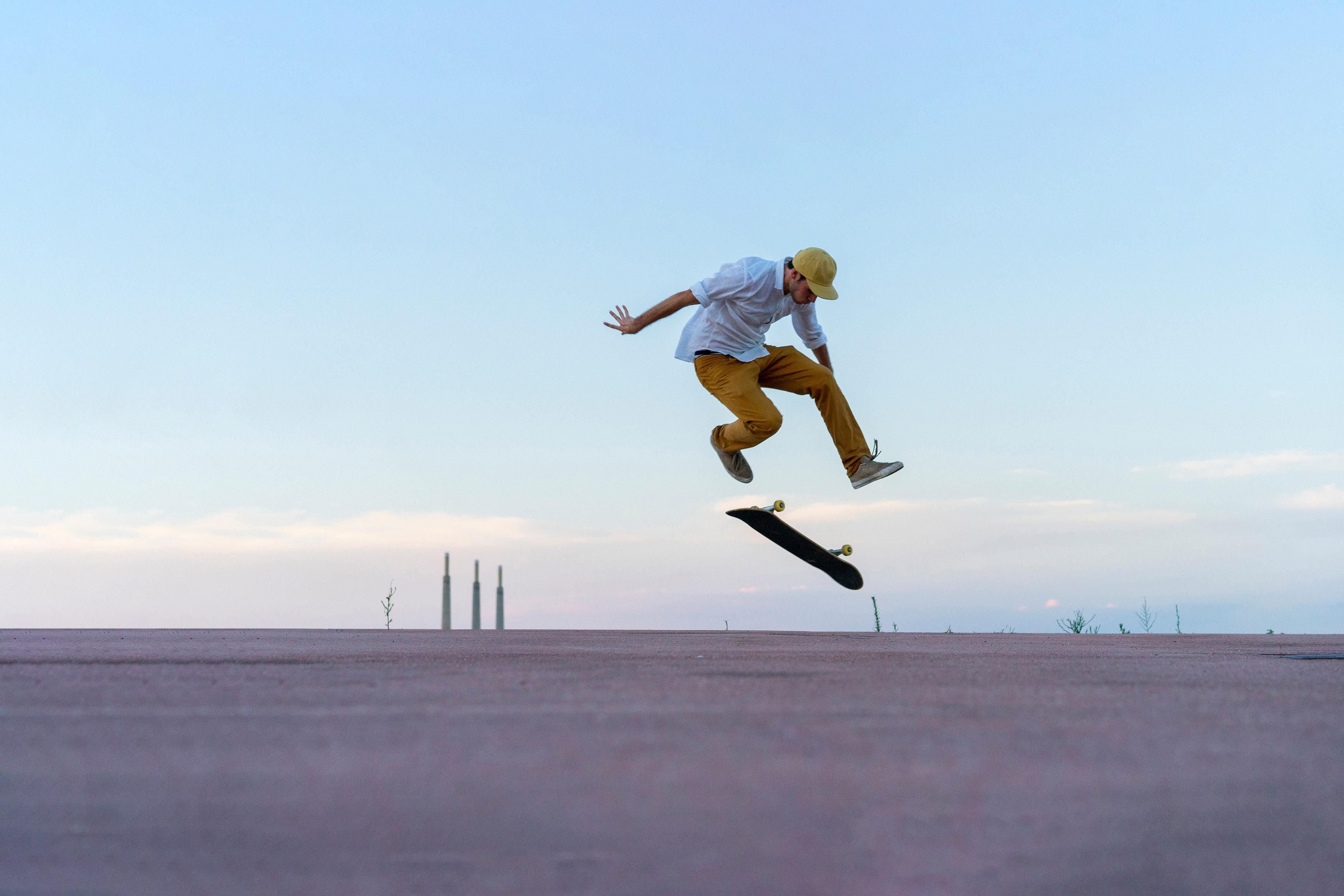 Man doing a skateboard trick on a lane at dusk